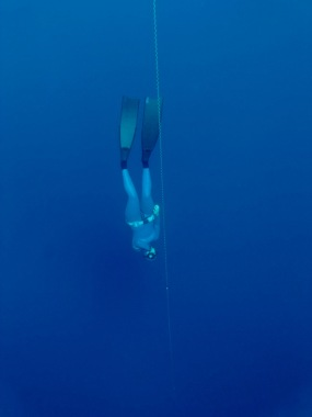 Kyla making small adjustments with her fins as she freefalls into Romblon's deep blue.