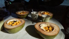 Our team's fresh, healthy and simple breakfast of porridge with mangoes, bananas and raisins in a fresh young coconut bowl.